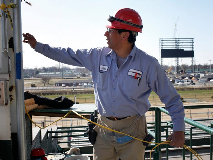 """Oscar Calderon runs wiring for temporary lighting in the new Grandstand Terrace and Rooftop Garden section of Churchill Downs Racetrack with a view of the outdoor video board being constructed in the background on the right. In addition to the expasion and renovation of the Grandstand Terrace is the construction of the """"World's Largest"""" outdoor video board that measures 90-feet by 171-feet. The projects total more than $26.5 million. March 26, 2014"""