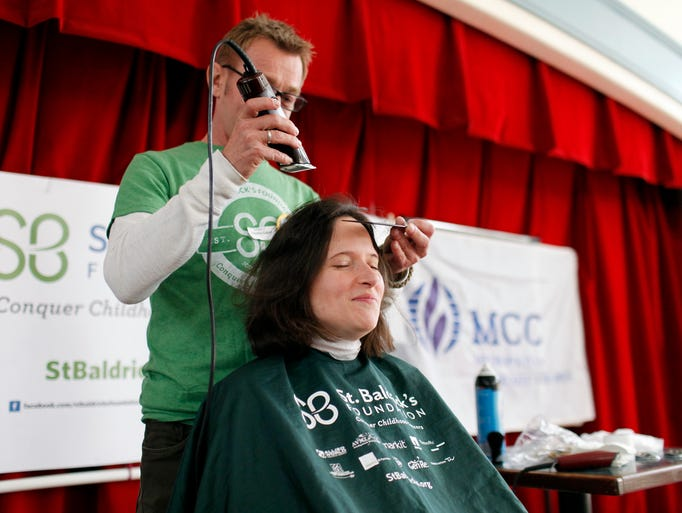 Monica Boyer waits for professional barber Timothy Capps to begin shaving her head during the St. Baldrick's Foundation event at the Metropolitan Community Church in Louisville. More than a dozen people shaved their head to raise money for St. Baldrick's Foundation during the intimate event, which helps raise money for childhood cancer research grants.  April 6, 2014