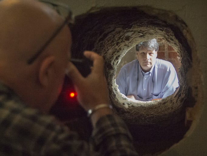 """The Sun"" newspaper reporter Paul Thompson poses for photographer Chris Bott in the cell wall hole  where Tim Robbins made his escape in the movie ""Shawshank Redemption."""