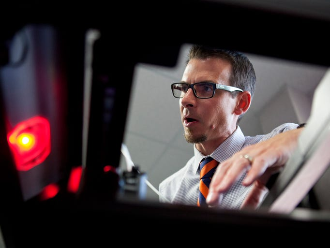 Benjamin Zombek, founder of BZDesign, talks about printing products with a 3-D printer to observes in High Tech Rochester in Henrietta on Tuesday, August 5, 2014.