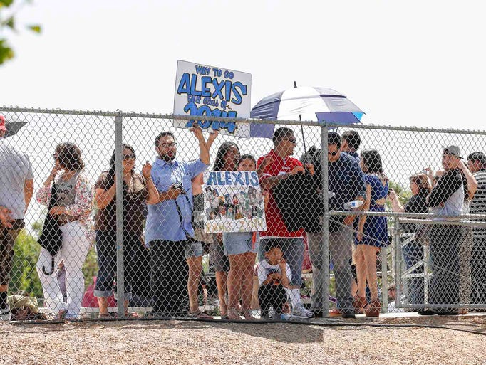 Supporters wave signs as they wait for their graduate to pass by at the start of commencement ceremonies at Everett Alvarez High School, Thursday, May 29, 2014 in Salinas, Calif. Vernon McKnight/for The Californian