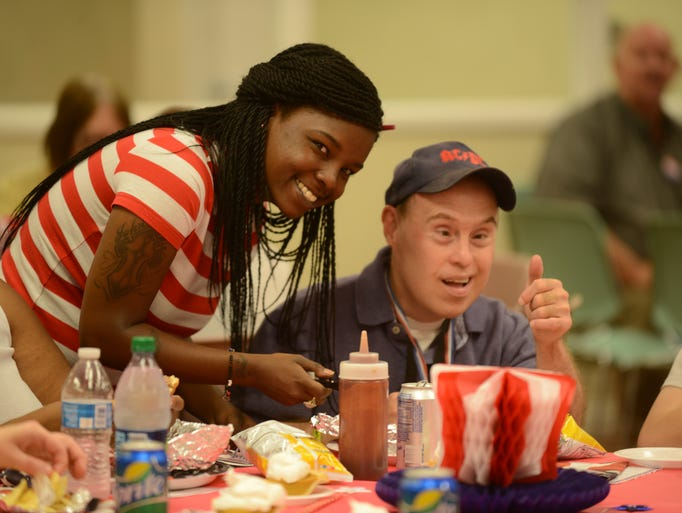 Crystal Eskridge (at left) helps Jeffrey Rogers (at right) with his barbecue sandwich Friday at the Jackson Center For Independent Living's celebration of the 24th anniversary of the signing of the Americans with Disabilities Act.