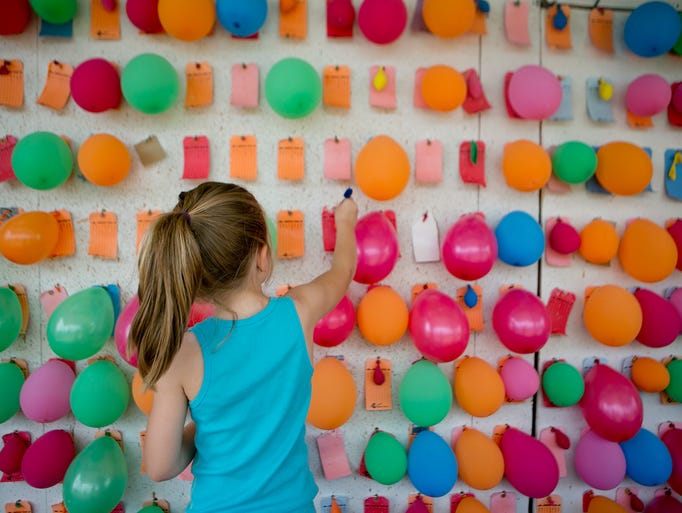 Analeza Gagnon of Green Bay helps hang up balloons at her mom, Jenny's game stand at the Taylor County Fair in Medford, Thursday, July 24, 2014. Jenny Gagnon is working with S+J Enterprises, which put on the carnival.