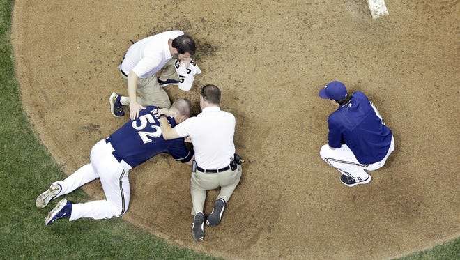 Milwaukee Brewers starting pitcher Jimmy Nelson lays on the ground after being hit in the head by a ball hit by St. Louis Cardinals' Thomas Pham during the third inning on Thursday in Milwaukee.