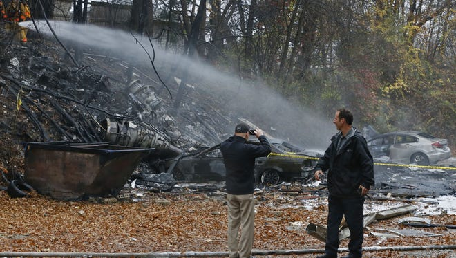 Terry Ellis, left, takes photos as firefighters work at the scene where authorities say a small business jet crashed into an apartment building in Akron, Ohio, Tuesday, Nov. 10, 2015. Investigators were trying to determine how many people were on the 10-seater jet, but they confirmed two deaths, said Lt. Sierjie Lash, an Akron fire department spokeswoman.