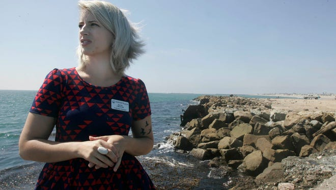 Kate Crouse, curator and collections manager at the Channel Islands Maritime Museum in Oxnard, talks about the wreck of the La Jenelle, a passenger ship that ran aground in a storm off the Port of Hueneme in 1970. The wreckage was used to form the breakwater in the photo behind Crouse.