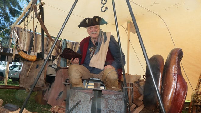 With his bear-fat-oiled moccasins drying by the fire, Gary Marciniak of the Smoky Hollow Muzzleloaders group relaxes in his tent amidst artifacts, tools, weapons and other authentic items of a 1750s French trader in Wisconsin, as part of a previous Old Falls Village Days. This year's event is Saturday and Sunday, June 2-3.