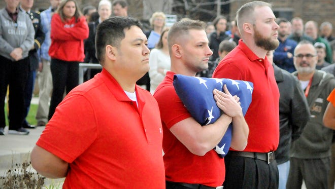 Matthew Deno, center, President of the Student Veterans Organization at St. Cloud Technical and Community College, holds a flag on Wednesday. Members of the SVO raised the new flag in a Veterans Day ceremony.
