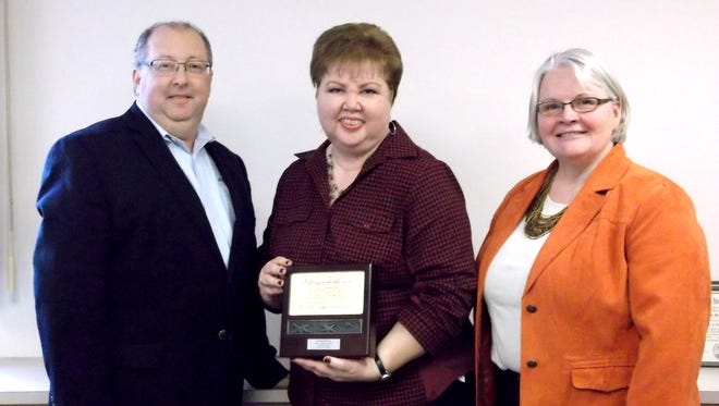 Brenda Robinson, center, payroll specialist for SpiriTrust Lutheran Home Care & Hospice, accepts the 2015 Karen A. Rohaly Award from Robert Rundle, CEO, SpiriTrust Lutheran, left; and Terry J. Shade, CEO, SpiriTrust Lutheran Home Care & Hospice, right.