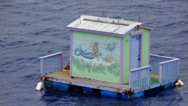 In this Wednesday, Aug. 2, 2017 photo provided by the U.S. Coast Guard, a tiny house with a mermaid on the side floats adrift in the Gulf of Mexico south of Grand Isle, La. The Coast Guard asks the public for any information regarding the dock.