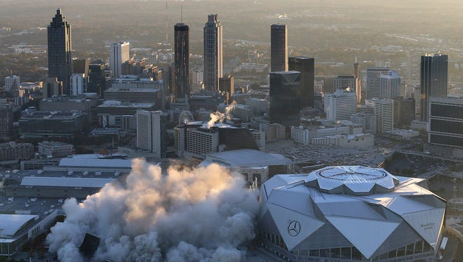 The Georgia Dome is destroyed in a scheduled implosion next to its replacement the Mercedes-Benz Stadium, right, on Nov. 20, 2017, in Atlanta.