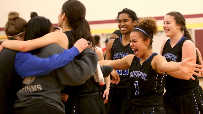 Olympic's (left to right) Kahlisha Grant, Kiki Mitchell and Emma Meadows celebrate their win over Renton on the court at Mount Tahoma High School Friday, Feb. 24, 2017.