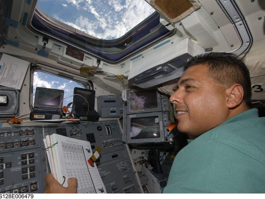 Astronaut José Hernández, STS-128 mission specialist, works on the flight deck of space shuttle Discovery during flight day two.