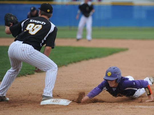 Hagerstown's Trey Kelley slides in safely at first base against Pioneer during the IHSAA Class A baseball regional semifinal at Carroll (Flora) Saturday, June 4, 2016.