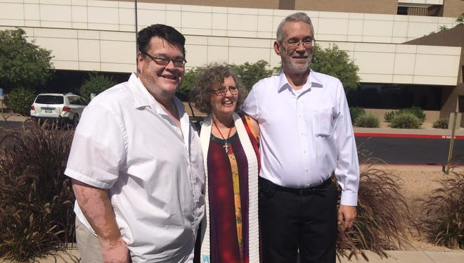 Rudy Armijo, left, and Don Pack hug minister Mary Jacobs after their Mesa wedding, which Jacobs officiated.