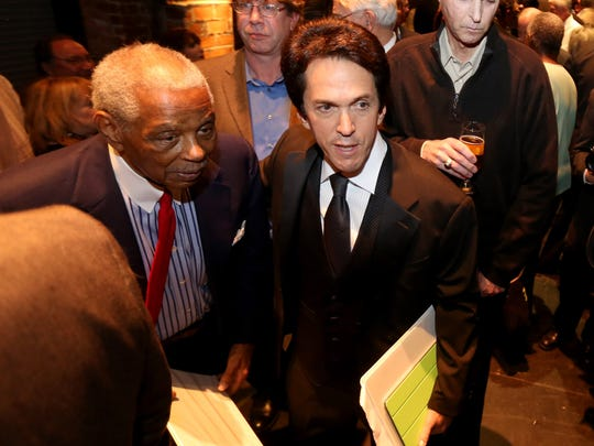 Judge Damon Keith, left, and Detroit Free Press columnist Mitch Albom make their way through the crowd at a book launch Nov. 11, 2013, in Detroit.