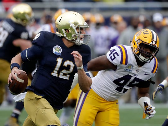 Notre Dame quarterback Ian Book (12) shambles for yardage past LSU linebacker Michael Divinity Jr. (45) during the first half of the Citrus Bowl NCAA college football game, Monday, Jan. 1, 2018, in Orlando, Fla.