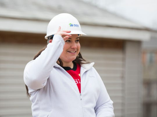 Meredith Cook puts on her hardhat on before she turns the dirt at the groundbreaking ceremony for the 58th Henderson Habitat Home on Friday afternoon.