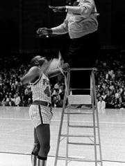 In 1966, Pearl senior Perry Wallace gets the net from Vanderbilt athletic employee Richard Baker after the end of the game against Memphis Treadwell. The unbeaten Pearl, with four Negro National championships in their bag, conquered a new world when they smacked Treadwell 63-54 in the finals of their first TSSAA State tournament.