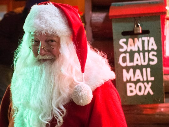 Santa Claus poses for a photo in front of his cabin, which has been used in Hanover for nearly 80 years, in 2017. A new Santa's Cabin will be used in 2018.