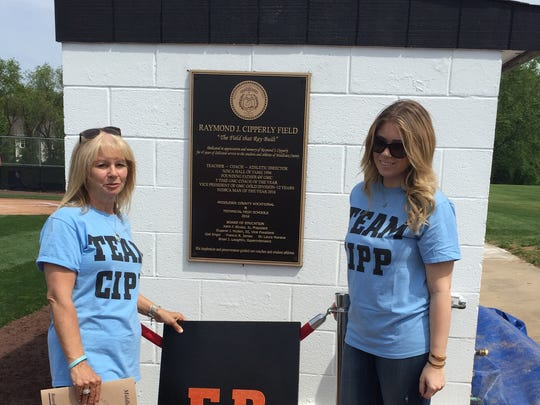Susan Cipperly (L) and Lauren Cipperly stand in front of plaque commemorating Ray Cipperly