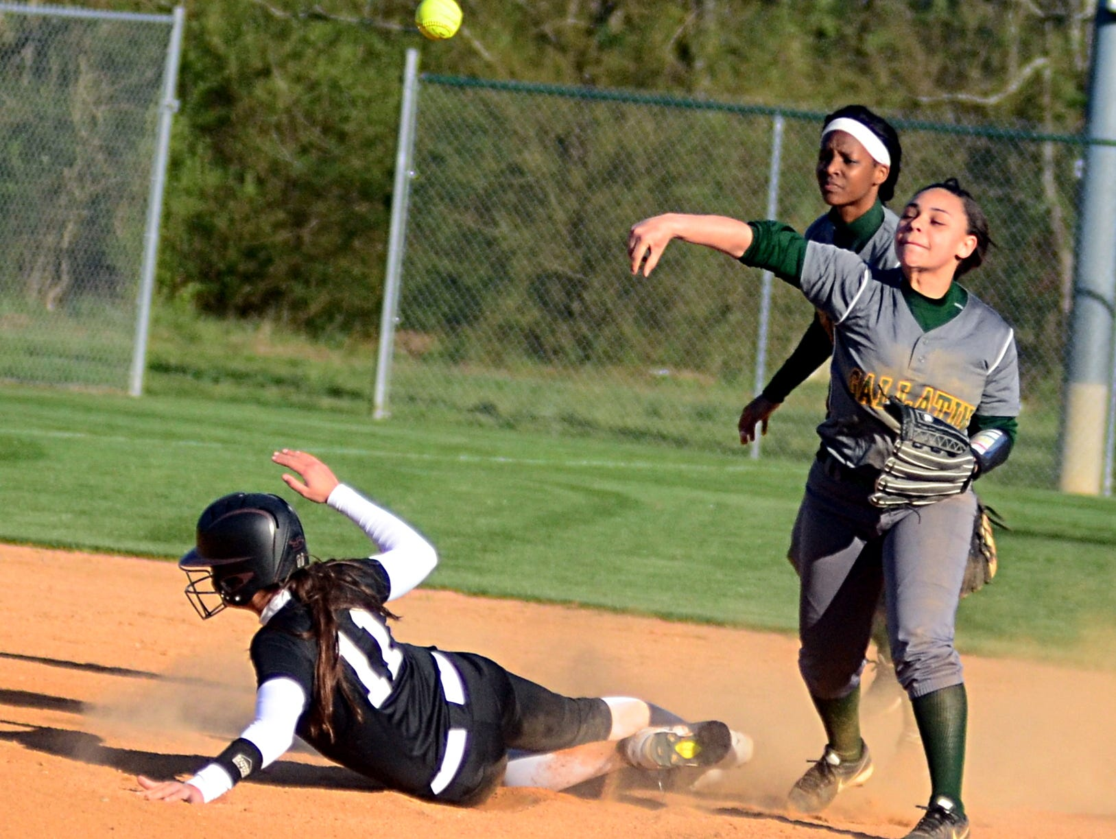 Gallatin High junior second baseman Ashlee Banks throws to first base as Station Camp senior Taylor Gaines slides safely into second base during first-inning action. Banks had one hit in the Lady Wave's 12-4 loss.