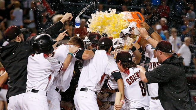 The Diamondbacks players surround Paul Goldschmidt after his walk-off home run against the Atlanta Braves in the ninth inning on Monday, Aug. 22, 2016, in Phoenix.