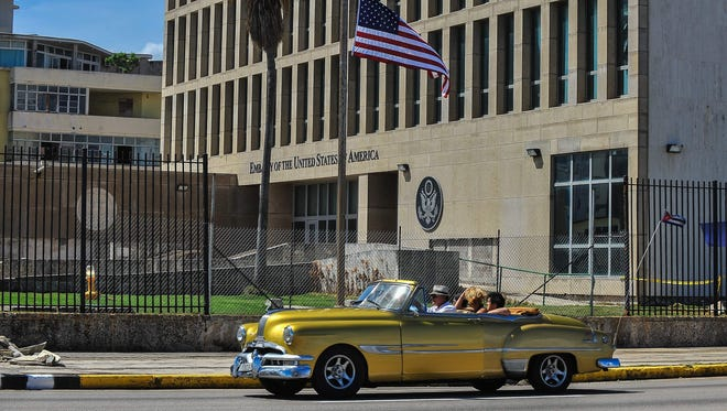 In this file photo taken on Oct. 3, 2017 a car drives by the U.S. Embassy in Havana.
