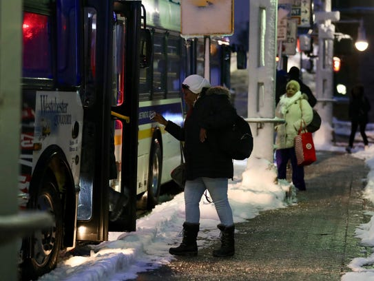 Commuters board a bus for the city at the Yonkers train