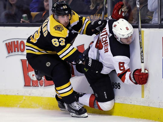 Boston Bruins left wing Brad Marchand (63) checks New