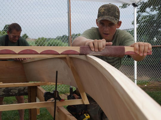 Carson Watts, 14, of Harbeson, uses a sanding bar to level off the bottom of his skiff's hull during the Family Boat Building Weekend in Lewes on Saturday. The Lewes Historical Society's volunteers coached families over three days as they built seaworthy, 12-foot skiffs.