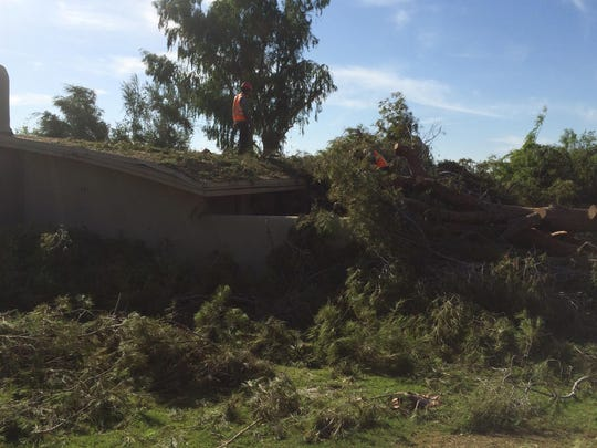 Crews clear away a tree that toppled onto a California Villas apartment on Elkhorn Trail in Palm Desert on July 30. Cleanup and repairs from the storm, which hit the Palm Desert Country Club area particularly hard, continue.