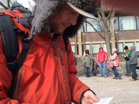 Paul Godin, 21, displays a money order Friday that will clear his backlog of traffic tickets. Godin joined more than 1,000 people in line at the Costello Courthouse in Burlington for a lenient treatment of fines.