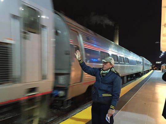 Rev. John Koski, associate pastor of Springwells Church in Dearborn, waves as the trains departs.