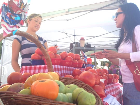 Shoppers explore the heirloom tomatoes sold at the
