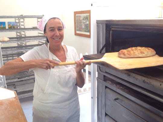 Kathleen McCloskey pulls fresh focaccia out of her stone hearth oven at New England Bakery & Cafe in south Fort Myers.