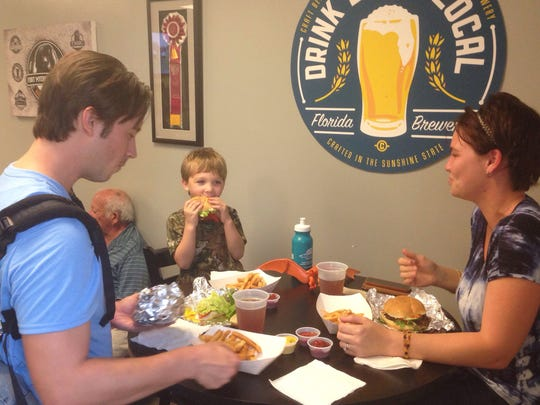 Dominic Leotti enjoys burgers from The Nosh Truck at the Brewery with his son, Galen, and wife, Carly.