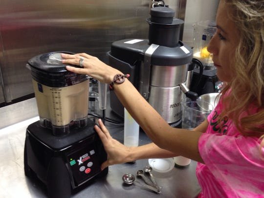 Karen Livreri, owner of smoothie and juice bar Juicy Juicy in Bermuda Dunes, blends the ingredients for bulletproof coffee in a high-speed blender.