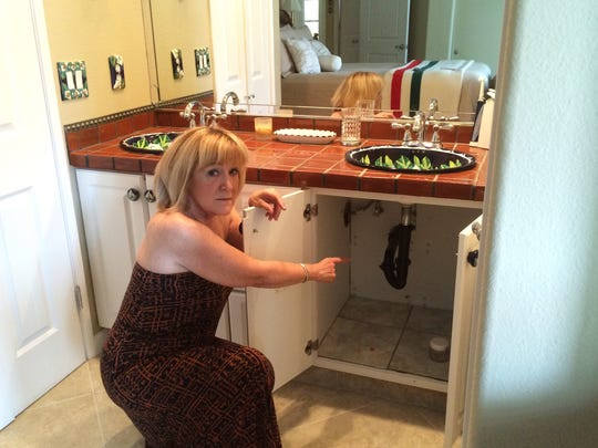 Diane Scurlock of La Quinta points to a cabinet in her bathroom, which was damaged in the storm.