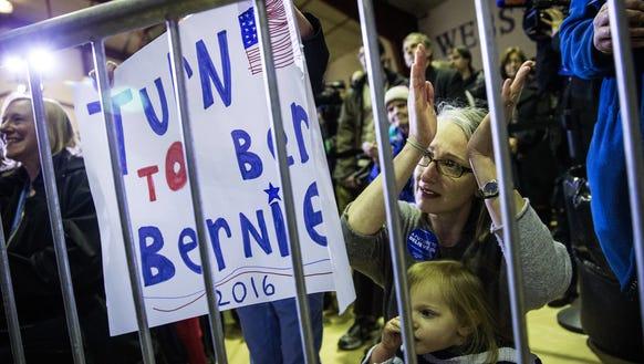 Audience members listen to Bernie Sanders speak at