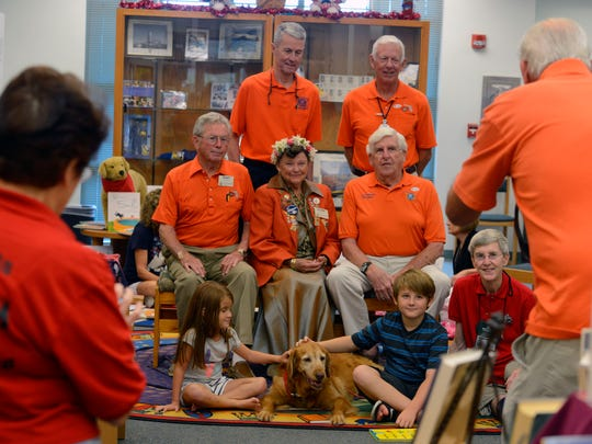 Members of the Kiwanis Club of Big Lagoon get their poto taken with Molly Saturday morning during the READ (Reading Education Assistance Dog) to the Dogs program at the Southwest Branch Library. Molly is retiring from the program after 10 years on the job.