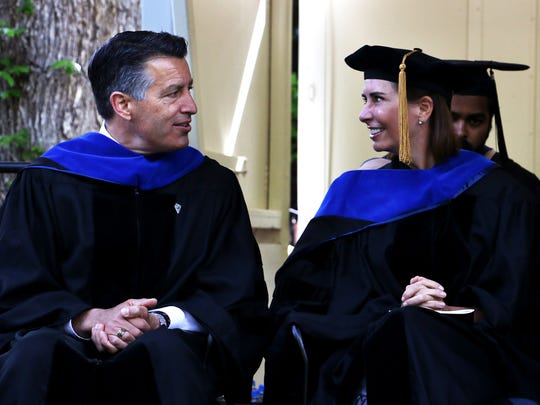 Lauralyn McCarthy, right, and Governor Brian Sandoval sit together during the University of Nevada, Reno commencement ceremony on Saturday morning, May 19, 2018.