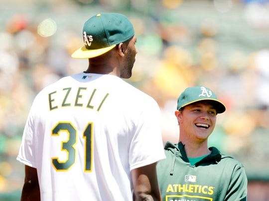 Oakland A's pitcher Sonny Gray, right, laughs while talking with Golden State Warriors center Festus Ezeli before Ezeli threw out the first pitch in June. Both were standout athletes at Vanderbilt.