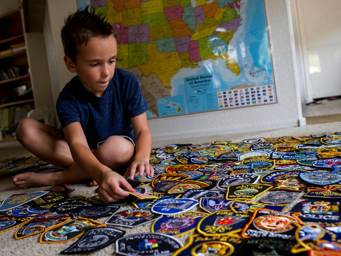 Caleb Benedetto, 6, looks through his collection of