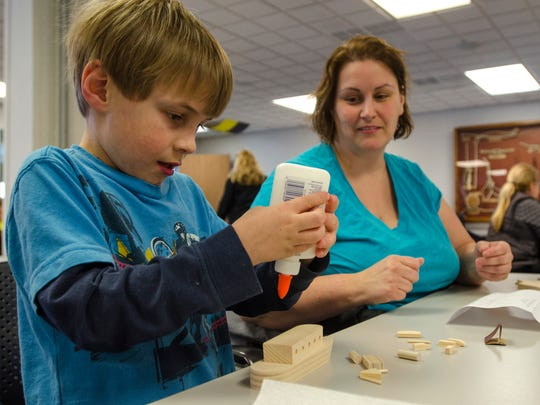 Evan Donahue, 7, of Marysville, tries to glue a piece of his model ship together Saturday, April 2, at the Maritime Center in Port Huron.