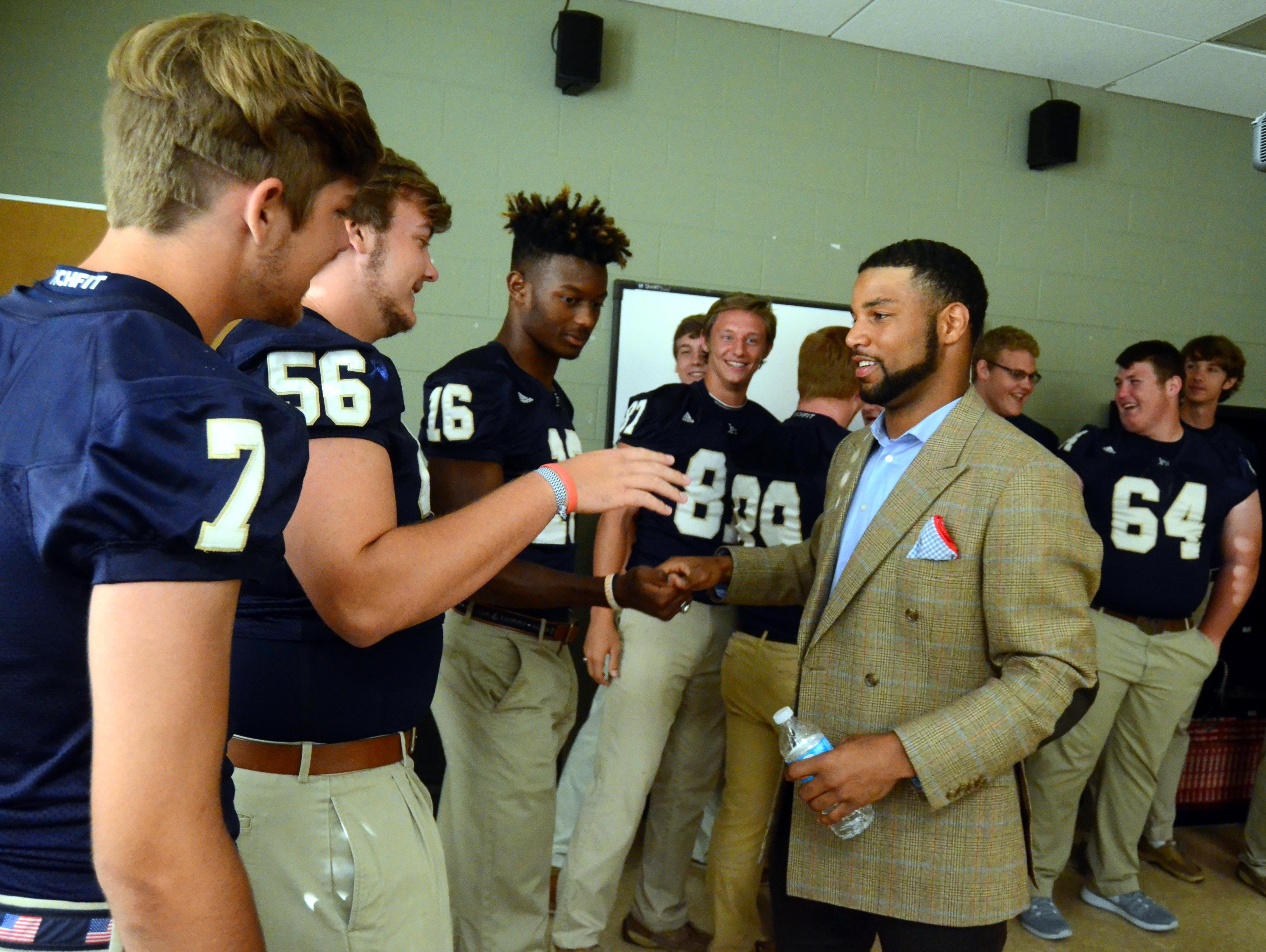 Detroit Lions wide receiver Golden Tate greets senior members of the Pope John Paul II High football team on Thursday evening, when the school retired his number.