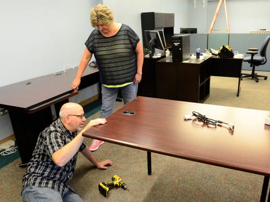 Lee Wyss, left, with information technology, and Karen Nahm, account clerk in the finance department, install a desk at Terra State for the county's move.