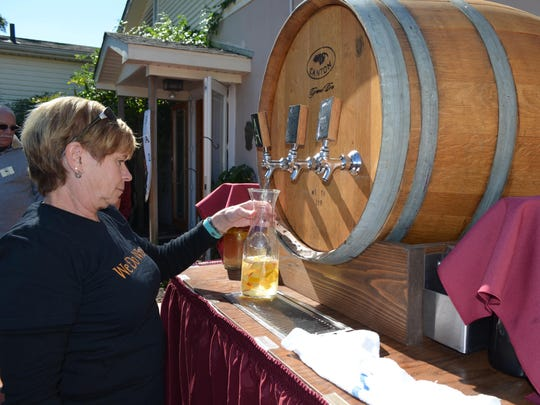 Flo Werning of Bellview Winery serves a botte of spiced apple sangria during the Italian Festival at the winery Oct. 15.