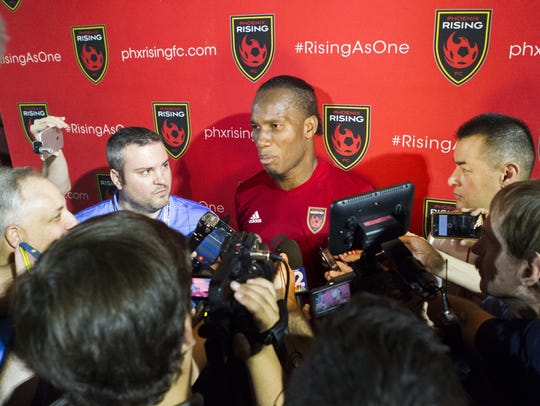 Didier Drogba (center) answers questions from reporters