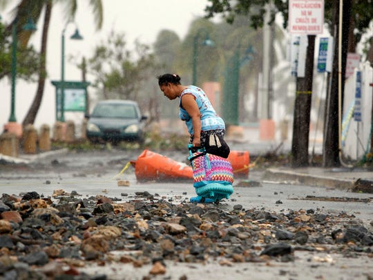 A woman pulls a travel case on a rock scattered road